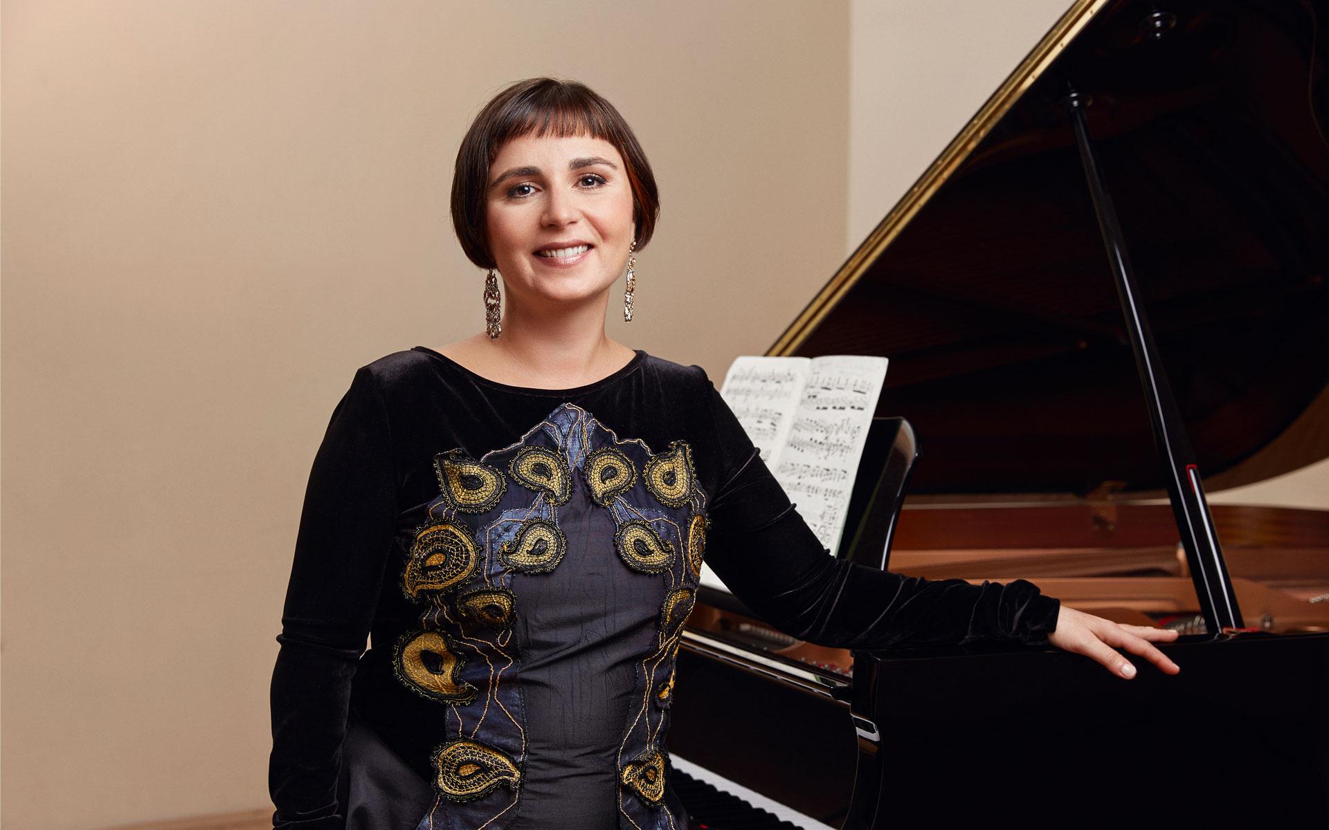 Startbild Natali Pavlovic steht vor dem Klavier